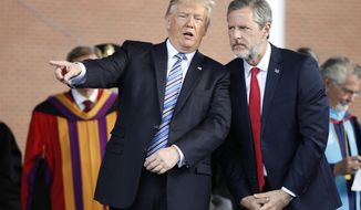 President Donald Trump gestures as he stands with Liberty University president, Jerry Falwell Jr., right, during commencement ceremonies at the school in Lynchburg, Va., Saturday, May 13, 2017. (AP Photo/Steve Helber)
