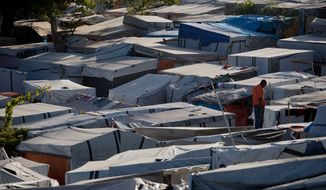 FILE - In this July 22, 2011 file photo, a man stands on a tent's roof at a refugee camp, once a golf course, set up for people displaced by the 2010 earthquake in Port-au-Prince, Haiti. The number of Haitians displaced by the earthquake has dropped since February, according to the International Organization for Migration. They say the drop marks the steepest decline in the camp population since early last year.  (AP Photo/Eduardo Verdugo, File)