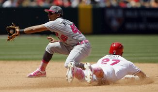 Los Angeles Angels' Mike Trout, right, steals second as Detroit Tigers shortstop Dixon Machado makes the catch during the fifth inning of a baseball game in Anaheim, Calif., Sunday, May 14, 2017. (AP Photo/Alex Gallardo)