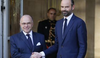 Newly appointed French Prime Minister Edouard Philippe, right, shakes hands with outgoing Prime Minister Bernard Cazeneuve in Paris, Monday, May, 15, 2017. French President Emmanuel Macron has appointed Philippe, a relatively unknown 46-year-old lawmaker, as prime minister, making good on campaign promises to repopulate French politics with new faces. (AP Photo/Francois Mori)
