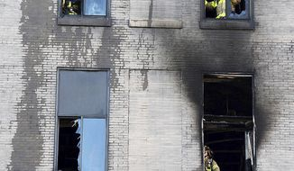 Firemen stand behind broken windows on the backside of Midtown Towers facing Penn Ave. in downtown Pittsburgh, Pa., where most of the exterior bricks were stained by smoke and flames early Monday, May 15, 2017.  Arson and homicide investigators were at the scene to determine the cause of the blaze that forced more than 100 residents to be evacuated from Midtown Towers, a 17-story building that houses apartments on its upper floors and a convenience store on its ground floor. (Darrell Sapp/Post-Gazette via AP)