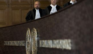 Presiding judge Ronny Abraham of France, left, enters the court room in The Hague, Netherlands, Monday, May 15, 2017. India is taking Pakistan to the United Nations' highest court in an attempt to save the life of an Indian naval officer sentenced to death last month by a Pakistani military court after being convicted of espionage. (AP Photo/Peter Dejong)