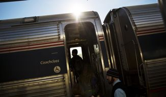 FILE - In this Nov. 23, 2016, file photo, passengers board an Amtrak train heading to New Orleans in Atlanta. An Amtrak passenger tweeted on Sunday, May 14, 2017, that he ordered a pizza to a stalled train traveling from New York to Washington, D.C. (AP Photo/David Goldman, File)