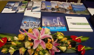 This Sunday, Jan. 15, 2017 photo shows pamphlets about investment immigration to various countries displayed outside a seminar by an investment group pitching ski resorts and other projects as a way of securing a EB-5 visa to immigrate to the U.S. in Beijing, China. (AP Photo/Ng Han Guan)