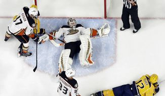 Anaheim Ducks goalie John Gibson sprawls on the ice after making a stop against Nashville Predators center Mike Fisher (12) during the first period in Game 3 of the Western Conference final in the NHL hockey Stanley Cup playoffs Tuesday, May 16, 2017, in Nashville, Tenn. (AP Photo/Mark Humphrey)