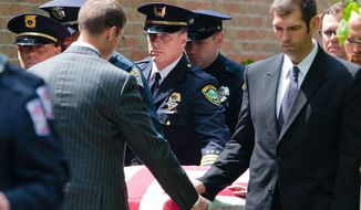 Norton Shores Police Department Lt. Michael Kasher helps wheel out the casket of Norton Shores police officer Jonathan Ginka as it exits Prince of Peace Catholic Church on Tuesday, May 16, 2017, in North Muskegon, Mich. Ginka was killed after his police cruiser struck a tree in the early morning hours of May 10, 2017, along Henry Street between Ross and Forest Park Roads in Norton Shores. (Joel Bissell /Muskegon Chronicle via AP)