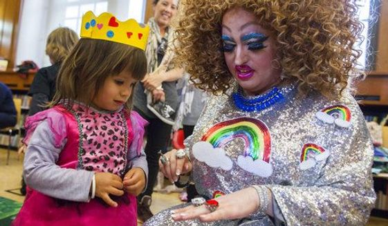 In this Saturday, May 13, 2017 photo, Lil Miss Hot Mess, right, compares outfits with 2-year old Eva McInnes after reading to a group of children during the Feminist Press' presentation of Drag Queen Story Hour at the Park Slope Branch of the Brooklyn Public Library in New York City. (AP Photo/Mary Altaffer)