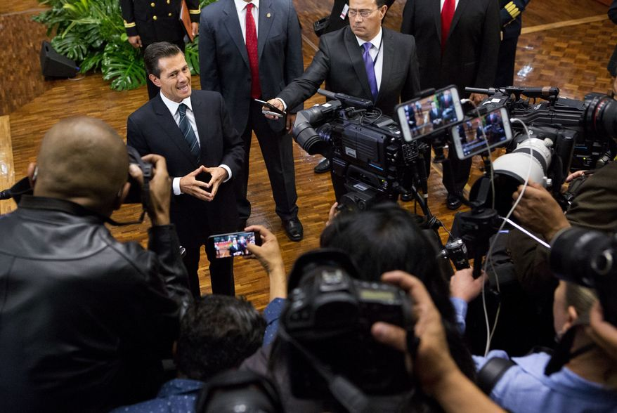 Mexico's President Enrique Pena Nieto, top left, pauses while speaking to the press, at the end of a press conference where he announced measures intended to protect journalists, in Mexico City, Wednesday, May 17, 2017. Pena said he is taking actions to halt slayings of journalists, without giving specifics, and promised more resources to help those under threat. Past measures have been ineffective in stopping the bloodshed among the country's media workers. (AP Photo/Rebecca Blackwell)