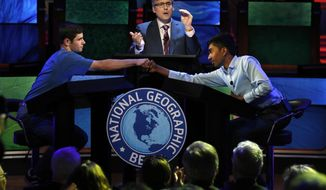 Host Mo Rocca applauds at center as Thomas Wright, 14, of Milwaukee, Wis., left, congratulates Pranay Varada, 14, of Carrollton, Texas, on winning the 2017 National Geographic Bee, Wednesday, May 17, 2017, at the National Geographic Society in Washington.  (AP Photo/Jacquelyn Martin)