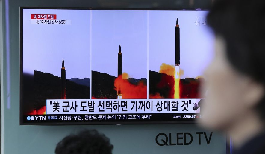 """A woman walks by a TV news program showing images of North Korean missile launch, published in the country's Rodong Sinmun newspaper, at Seoul Railway station in Seoul, South Korea, Monday, May 15, 2017. North Korea said Monday the missile it launched over the weekend was a new type of """"medium long-range"""" ballistic rocket that can carry a heavy nuclear warhead. A jubilant leader Kim Jong Un promised more nuclear and missile tests and warned that North Korean weapons could strike the U.S. mainland and Pacific holdings. (AP Photo/Lee Jin-man)"""