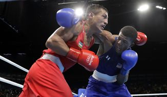 Uzbekistan's Fazliddin Gaibnazarov, left, and United State's Gary Russell exchange punches during a men's light welterweight 64-kg quarterfinals boxing match at the 2016 Summer Olympics in Rio de Janeiro, Brazil, Tuesday, Aug. 16, 2016. (AP Photo/Jae C. Hong)