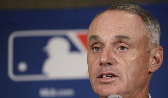 """FILE - In this Feb. 21, 2017, file photo, Major League Baseball Commissioner Rob Manfred answers questions at a news conference in Phoenix. Baseball fans can like their team's games with a click starting Friday. Major League Baseball announced Facebook will carry a live game nationally each Friday starting with Colorado at Cincinnati this week. The Facebook package of 20 games will use the broadcast feed of one of the involved teams. Baseball Commissioner Rob Manfred made the announcement Thursday, May 18, 2017. He calls it """"really important for us in terms of experimenting with a new partner in this area.""""(AP Photo/Morry Gash, File)"""