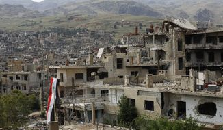 A huge Syrian National flag hangs out of a damage building at the mountain resort town of Zabadani in the Damascus countryside, Syria, Thursday, May 18, 2017. A U.S. airstrike struck pro-Syrian government forces for the first time, hitting a convoy in the desert near the border with Jordan, U.S. officials and Syrian activists said, an apparent signal to President Bashar Assad to keep his forces out of a zone where U.S.-backed rebels are fighting the Islamic State group. (AP Photo/Hassan Ammar)