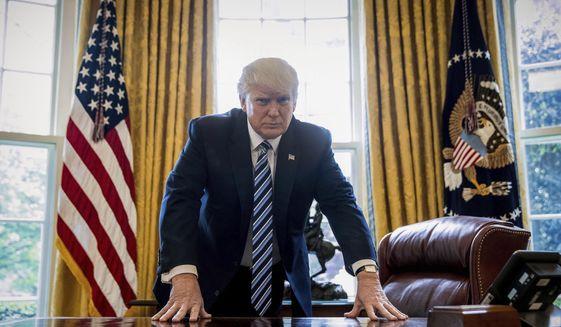 President Donald Trump at his desk in the Oval Office.