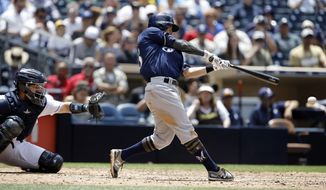 Milwaukee Brewers' Eric Sogard, right, hits a run scoring single as San Diego Padres catcher Luis Torrens watches during the fifth inning of a baseball game in San Diego, Thursday, May 18, 2017. (AP Photo/Alex Gallardo)