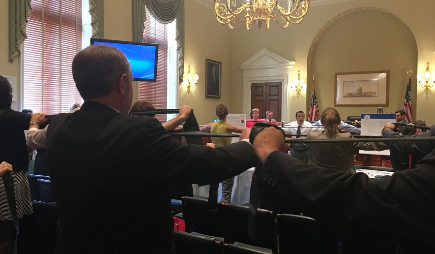 Attendees of a congressional information session on physical fitness work out on resistance bands in a short exercise demonstration on May 18. (Laura Kelly/The Washington Times)