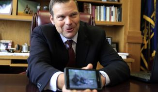 In this Wednesday, May 17, 2017 photo, Kansas Secretary of State Kris Kobach shows family photos to a reporters in his office in Topeka, Kan. Kobach has been picked by President Donald J. Trump to help lead a new commission on election fraud.  (AP Photo/Orlin Wagner)