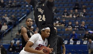 FILE - In this March 11, 2017, file photo, Central Florida's Tacko Fall (24) guards SMU's Ben Moore during the first half of an NCAA college basketball game in the American Athletic Conference tournament semifinals,in Hartford, Conn. UCF's 7-foot-6 sophomore center Tacko Fall decided this spring to explore his NBA options, but all indications are he is finding out that his best option may be to return to school for another season. (AP Photo/Jessica Hill, File)