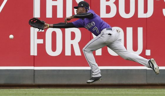 Colorado Rockies left fielder Raimel Tapia reaches in vain for a double by Minnesota Twins' Joe Mauer during the third inning in the second game of a baseball doubleheader, Thursday, May 18, 2017, in Minneapolis. (AP Photo/Jim Mone)