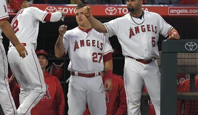 Los Angeles Angels' Andrelton Simmons, left, is congratulated by Mike Trout, center, and Albert Pujols after scoring on a triple by Ben Revere during the second inning of a baseball game, Wednesday, May 17, 2017, in Anaheim, Calif. (AP Photo/Mark J. Terrill)