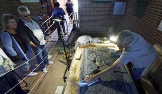 In this Tuesday, May 9, 2017 photo, monument Conservator Jonathan Appell, right, works to clean a 6-foot black stone slab which was rediscovered in the 1617 church at historic Jamestown, Va. Six months after launching a painstaking probe aimed at English America's second oldest church, Jamestown archaeologists have unearthed a jumbled historical puzzle that reaches back 400 years. (Aileen Devlin/The Daily Press via AP)