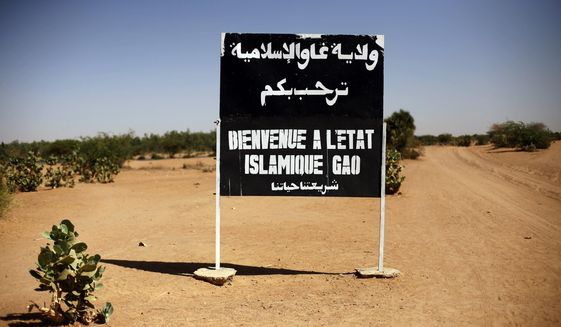 """FILE-- In this photo taken Wednesday Jan. 30, 2013, a sign on the northern road exiting in Gao, Northern Mali, reads """"welcome to the islamic state of Gao. France's new president Emmanuel Macron has chosen for his first official visit outside Europe the West African nation of Mali, a country where multiple extremist groups pose a growing danger to the region.(AP Photo/Jerome Delay, File)"""