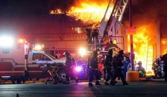 San Antonio firefighters gather at the scene of a fire Thursday, May 18, 2017, at Ingram Square in San Antonio, Texas.  A San Antonio firefighter has died and two others are seriously hurt after a fire swept through the local shopping mall, where parts of the building collapsed and forced crews to retreat. (Jacob Beltran/The San Antonio Express-News via AP)