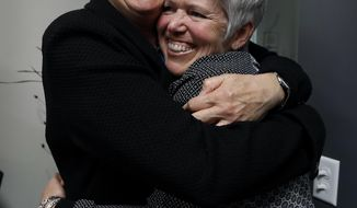 FILE - In this May 4, 2017, file photo, Jane Meyer, former senior associate athletic director at the University of Iowa, gets a hug from her partner Tracey Griesbaum, right, following a news conference in Des Moines, Iowa. The University of Iowa will pay $6.5 million to settle high-profile discrimination lawsuits filed by former athletic administrator Jane Meyer and her partner, former women's field hockey coach Tracey Griesbaum, according to settlements released Friday, May 19, 2017. (AP Photo/Charlie Neibergall, File)