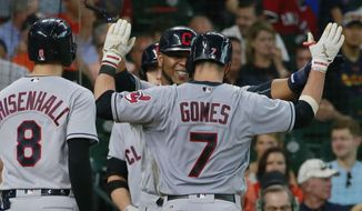 Cleveland Indians Yan Gomes (7) is greeted by Edwin Encarnacion and Lonnie Chisenhal after his three-run home run against the Houston Astros in the third inning of a baseball game Sunday, May 21, 2017, in Houston. (AP Photo/Richard Carson)