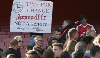 An Arsenal fan holds up a protest banner after the English Premier League soccer match between Arsenal and Everton at The Emirates stadium in London, Sunday May 21, 2017. (AP Photo/Tim Ireland)
