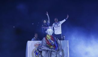 Real Madrid captains Sergio Ramos, top right, and Marcelo gestures to supporters next to the goddess Cibeles monument as they celebrate with teammates after winning the Spanish La Liga soccer tournament title at the Cibeles square in Madrid, Monday, May 22, 2017. Real Madrid has won the Spanish soccer championship on 33 times. (AP Photo/Francisco Seco)
