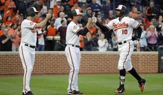 Baltimore Orioles' Seth Smith, left, and J.J. Hardy greet teammate Adam Jones after scoring on his three-run home run in the second inning of a baseball game against the Minnesota Twins in Baltimore, Monday, May 22, 2017. (AP Photo/Patrick Semansky)