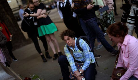 """A crowd gathered for a vigil in Albert Square on Tuesday to remember the victims of the terrorist attack that killed at least 22 people attending an Ariana Grande concert in Manchester, England on Monday. Prime Minister Theresa May said the United Kingdom's terrorism threat level was being raised to """"critical."""" (Associated Press)"""
