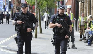 Armed police patrol the streets near to Manchester Arena in central Manchester, England, Tuesday May 23, 2017. An apparent suicide bomber attacked an Ariana Grande concert as the performance ended, killing 22 people as the audience filed out of the arena and sending frantic parents searching for their children amid a panicked crowd of young concertgoers. (AP Photo/Rui Vieira)