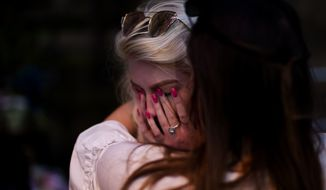 People cry after a vigil in Albert Square, Manchester, England, Tuesday May 23, 2017, the day after the suicide attack at an Ariana Grande concert that left 22 people dead as it ended on Monday night. (AP Photo/Emilio Morenatti)