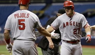 Los Angeles Angels' Mike Trout (27) celebrates with Albert Pujols (5) after Trout hit a home run off Tampa Bay Rays starting pitcher Alex Cobb during the first inning of a baseball game, Tuesday, May 23, 2017, in St. Petersburg, Fla. (AP Photo/Chris O'Meara)