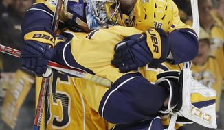 Nashville Predators defenseman Mattias Ekholm (14), of Sweden, jumps on goalie Pekka Rinne (35), of Finland, and left wing Viktor Arvidsson (38), of Sweden, after the Predators beat the Anaheim Ducks to win Game 6 of the Western Conference final in the NHL hockey Stanley Cup playoffs Monday, May 22, 2017, in Nashville, Tenn. The Predators won 6-3 to win the series 4-2 and advance to the Stanley Cup Finals. (AP Photo/Mark Humphrey)