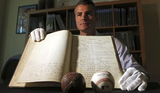 This May 18, 2017, photo shows Dan Imler, vice president of SCP Auctions, with the bound volume of the 1876 constitution that founded the National League of Professional Base Ball and the modern business of big league sports, that is going up for sale at SCP Auctions in Laguna Niguel, Calif. A replica of a period baseball is at left; a modern ball is at right.  SCP Auctions expects the papers to draw millions when the auction starts Wednesday, May 24. (AP Photo/Reed Saxon)