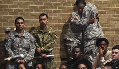 Bowie State University ROTC students comfort each other during a memorial vigil for Richard Collins III, who was killed Saturday at the University of Maryland in College Park, as they gather at Bowie State's auditorium in Bowie, Md., Monday, May 22, 2017. Authorities appealed for patience Monday from two college communities reacting in shock, fear and anger after a white University of Maryland student was arrested in what police called the unprovoked stabbing of a black Bowie State University student. (Kenneth K. Lam/The Baltimore Sun via AP)
