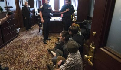 House State Government Committee Chairman Daryl Metcalfe, top left, looks on as demonstrators seeking a ban on gifts to lawmakers protest before being arrested at the Pennsylvania Capitol in Harrisburg, Pa., Tuesday, May 23, 2017. The March on Harrisburg demonstrators say they want a gift-ban bill that's been sitting in Metcalfe's committee since January to move forward. Group members say Metcalfe refuses to meet. (AP Photo/Matt Rourke)