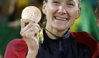 FILE - In this Aug. 18, 2016, file photo, United States' Kerri Walsh Jennings stands on the podium after winning the bronze medal in the women's beach volleyball competition of the 2016 Summer Olympics in Rio de Janeiro, Brazil. More than 100 athletes from around the world say the medals they won at the Rio Olympics are damaged. The IOC and Rio organizers plan to replace them with new medals.  Among those with defective medals are beach volleyball star Kerri Walsh Jennings who says her bronze medal from last summer is flaking and rusting. (AP Photo/Marcio Jose Sanchez, File)