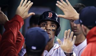 Boston Red Sox's Xander Bogaerts is congratulated by teammates after scoring on a wild pitch by Texas Rangers relief pitcher Jeremy Jeffress during the sixth inning of a baseball game at Fenway Park in Boston, Tuesday, May 23, 2017. (AP Photo/Charles Krupa)
