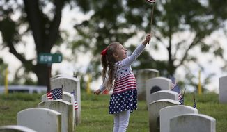 Four-year-old Grace Hendrian, of Quincy, Ill., stops to play with a small American flag while helping set the flags in front of tombstones in Sunset Cemetery Wednesday, May 24, 2017, on the grounds of the Illinois Veterans Home in Quincy, Ill. Scores of volunteers turned out to help place the flags in honor of Memorial Day. (Phil Carlson/Quincy Herald-Whig via AP)