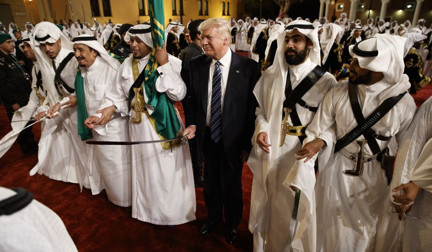 In this Saturday, May 20, 2017, file photo, President Donald Trump holds a sword and sways with traditional dancers during a welcome ceremony at Murabba Palace, in Riyadh. Trump and his entourage were treated to a traditional all-male Saudi sword dance. Standing shoulder-to-shoulder with the Saudi king, Trump swayed side to side and briefly joined the groove. (AP Photo/Evan Vucci, File)