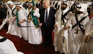 FILE - In this Saturday, May 20, 2017 file photo, President Donald Trump holds a sword and sways with traditional dancers during a welcome ceremony at Murabba Palace, in Riyadh. Trump and his entourage were treated to a traditional all-male Saudi sword dance. Standing shoulder-to-shoulder with the Saudi king, Trump swayed side to side and briefly joined the groove. (AP Photo/Evan Vucci, File)