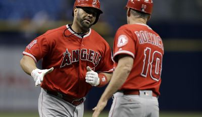 Los Angeles Angels' Albert Pujols, left, shakes hands with third base coach Ron Roenicke after Pujols hit a two-run home run off Tampa Bay Rays pitcher Erasmo Ramirez during the first inning of a baseball game Wednesday, May 24, 2017, in St. Petersburg, Fla. (AP Photo/Chris O'Meara)