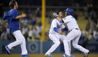 Los Angeles Dodgers' Logan Forsythe, right, celebrates with Adrian Gonzalez, center, and starting pitcher Clayton Kershaw after hitting an RBI double in the 13th inning of a baseball game against the St. Louis Cardinals, Tuesday, May 23, 2017, in Los Angeles. The Dodgers won 2-1. (AP Photo/Mark J. Terrill)