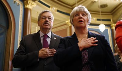 U.S. Ambassador to China and former Iowa Gov. Terry Branstad, left, and his wife Chris join in the Pledge of Allegiance before Lt. Gov. Kim Reynolds is sworn in as governor during a ceremonial swearing in, Wednesday, May 24, 2017, at the Statehouse in Des Moines, Iowa. (AP Photo/Charlie Neibergall)