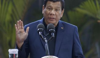 Philippine President Rodrigo Duterte gestures as he answers questions from reporters at Manila's international airport, Philippines, Wednesday, May 24, 2017. Duterte warned Wednesday that he'll be harsh in enforcing martial law in his country's south as he abruptly left Moscow to deal with a crisis at home sparked by a Muslim extremist siege on a city, where militants burned buildings overnight and are feared to have taken hostages. (AP Photo/Aaron Favila)