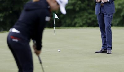 Eric Trump, right, watches as professional golfer Lydia Ko, of New Zealand, putts prior to the start of a news conference previewing the U.S. Women's Open Championship golf tournament at Trump National Golf Club, Wednesday, May 24, 2017, in Bedminster, N.J. (AP Photo/Julio Cortez)